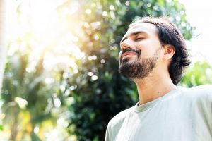 Bearded man looking content with the sun shining